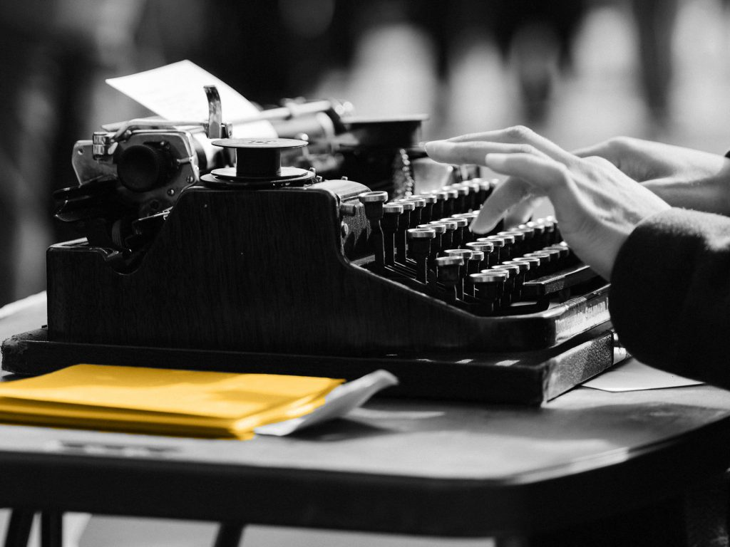 Writer using a typewriter to create ads headlines and descriptions